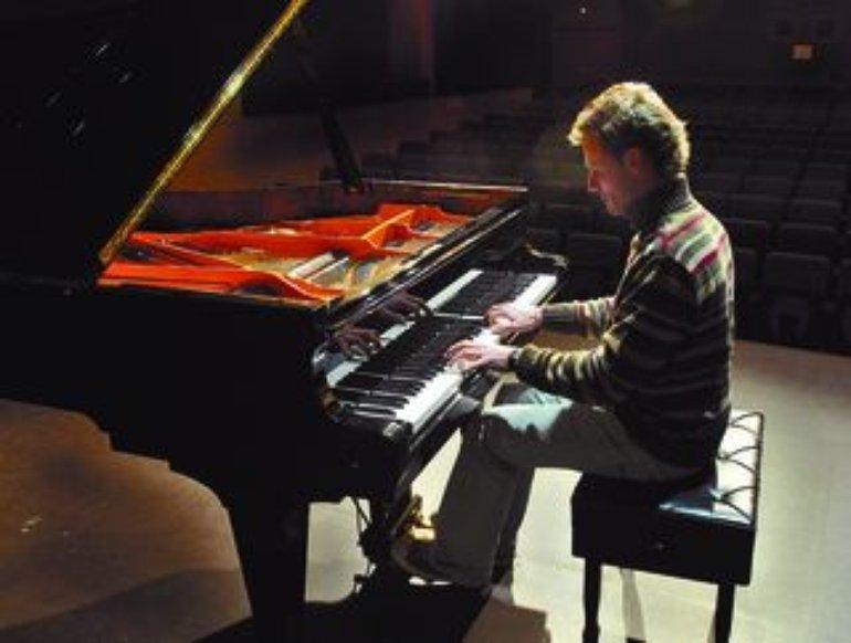 Mario López estuvo probando el piano de la Casa de Cultura antes de ofrecer el concierto de 1973.