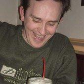 Питрович смотрит в пиво и улыбается.