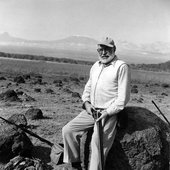 Ernest Hemingway sits on a large rock while holding a rifle in Africa.jpg