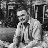 Ernest Hemingway sits in front of a building, Ketchum, Idaho.jpg